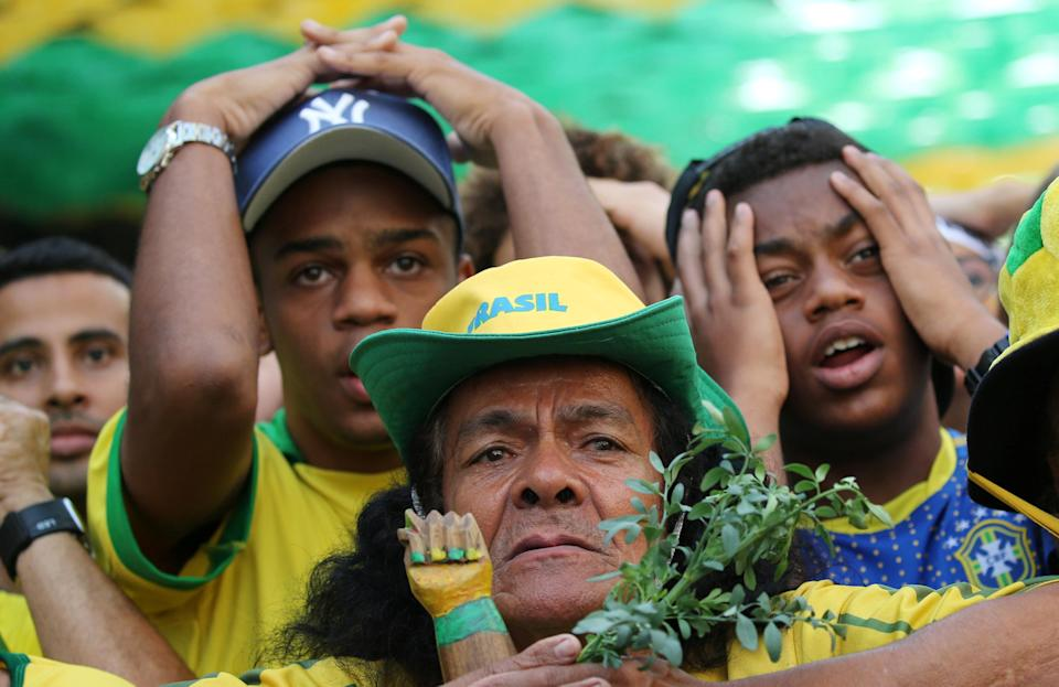 <p>Fans react during the match as they watch the broadcast. REUTERS/Sergio Moraes </p>