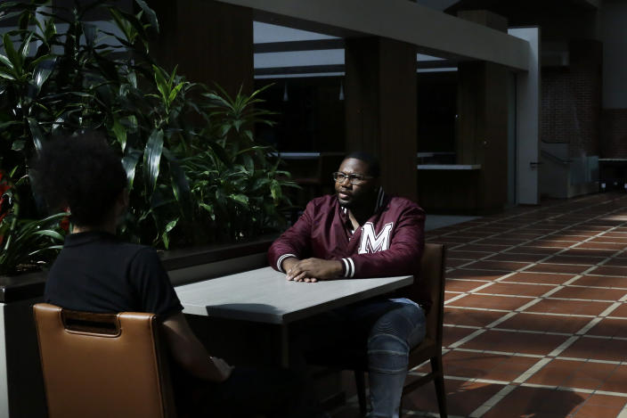 """In this Tuesday, May 5, 2020, photo, Morehouse College senior Lanarion """"LTL"""" Norwood Jr., of Atlanta, sits and talks with fellow student Joseph Ramirez in a hotel in Atlanta. Students were sent home from the college amid the new coronavirus outbreak. (AP Photo/Brynn Anderson)"""