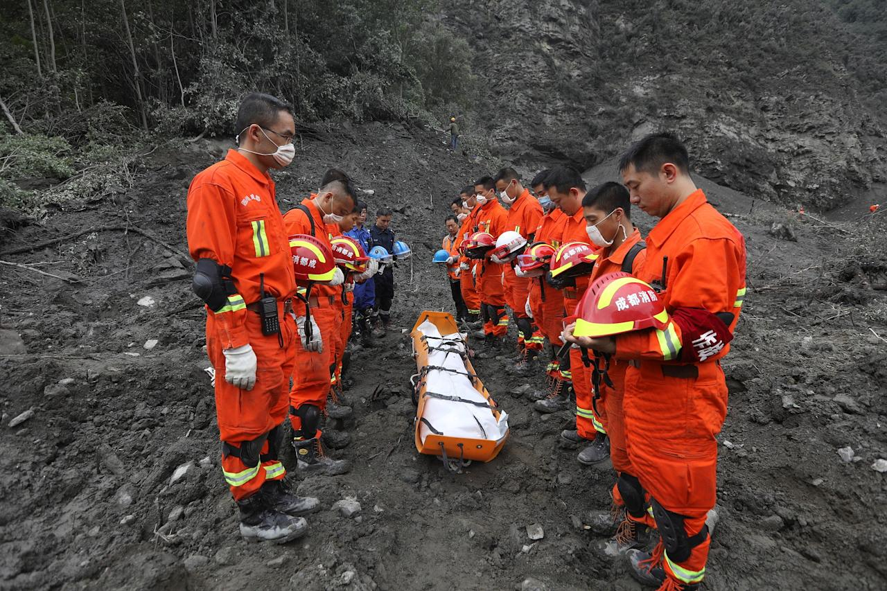 <p>Rescue workers stand in silent tribute before evacuating a body from the site of a landslide in the village of Xinmo, Mao County, Sichuan Province, China, June 25, 2017. (Photo: Stringer/Reuters) </p>
