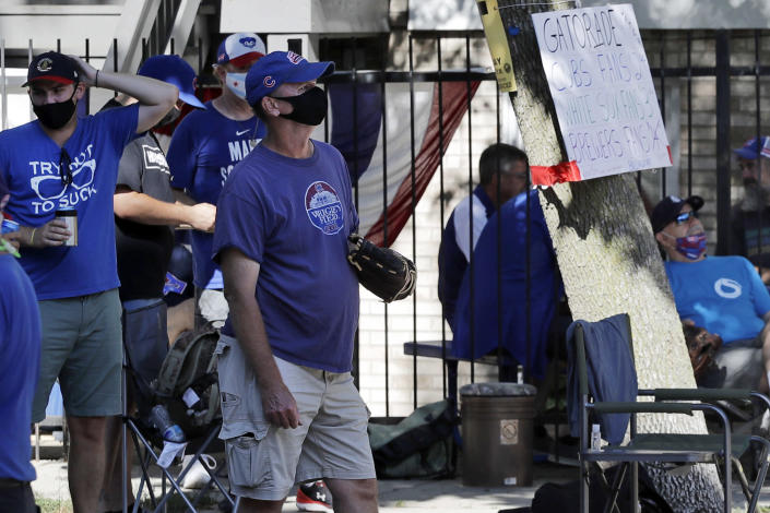 Chicago Cubs fans wait for a ball outside of Wrigley Field before the Opening Day baseball game between the Chicago Cubs and the Milwaukee Brewers in Chicago, Friday, July 24, 2020, in Chicago. In a normal year, that would mean a sellout crowd at Wrigley Field and jammed bars surrounding the famed ballpark. But in a pandemic-shortened season, it figures to be a different atmosphere. (AP Photo/Nam Y. Huh)