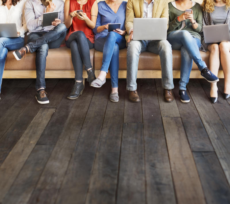 A group of people sitting on a bench, all holding laptops, tablets, or smartphones.