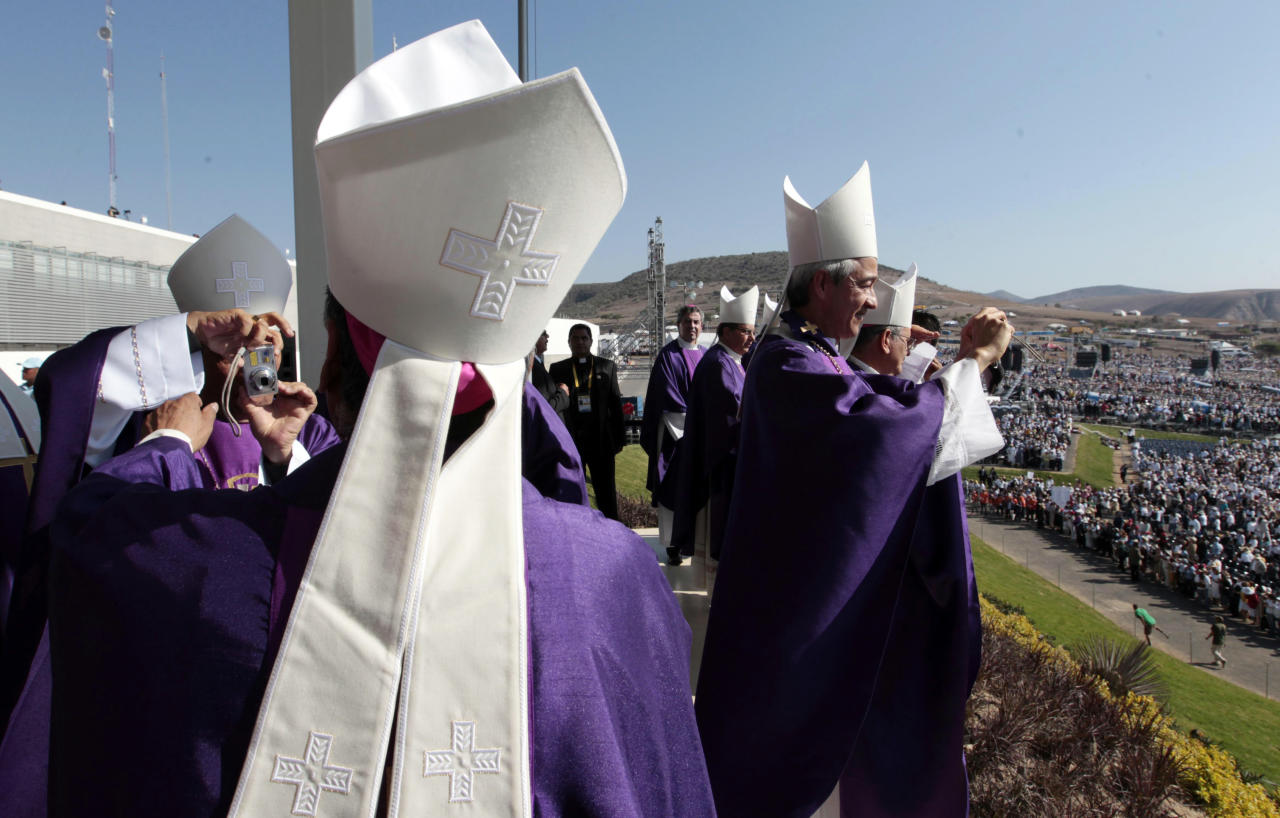 Prelates take pictures of each other and the crowd of faithful gathered at the Parque del Bicentenario as they wait for the arrival of Pope Benedict XVI for a Mass near Silao, Mexico, Sunday March 25, 2012. (AP Photo/Gregorio Borgia)