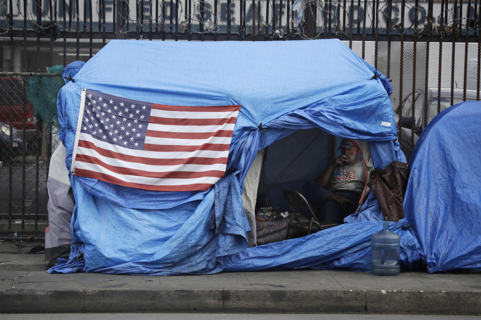 FILE - In this March 20, 2020, file photos, a man smokes inside a tent on skid row in Los Angeles. The 9th U.S. Court of Appeals on Thursday, Sept. 23, 2021, overturned a federal judge's sweeping order that required the city and county of Los Angeles to quickly find shelter for all homeless people living on downtown's Skid Row. (AP Photo/Marcio Jose Sanchez, File)