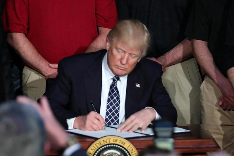Coal miners look on as US President Donald Trump signs an executive order rolling back Obama's climate change rules: REUTERS