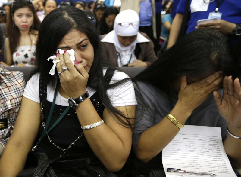 Overseas Filipino Workers, who fled the civil war in Syria, cry upon arriving at the Ninoy Aquino International Airport via a chartered flight by the International Organization for Migration on Tuesday, Sept. 11, 2012, in Manila, Philippines. The nearly 300 workers, all of them young women who worked as babysitters and maids in Syria, said they were scared for their safety and sought shelter at the Philippine Embassy in Damascus until their repatriation Tuesday. (AP Photo/Bullit Marquez)