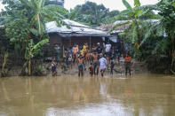 Rohingya refugees look at flood water following heavy rains at the Rohingya refugee camp in Kutupalong, Bangladesh, Wednesday, July 28, 2021. Days of heavy rains have brought thousands of shelters in various Rohingya refugee camps in Southern Bangladesh under water, rendering thousands of refugees homeless. (AP Photo/ Shafiqur Rahman)