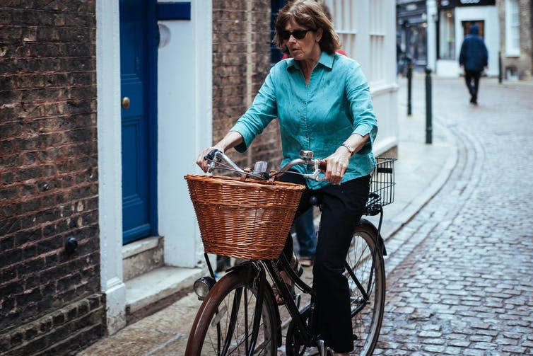 A woman passes a house on her bike with a wicker basket on the front.