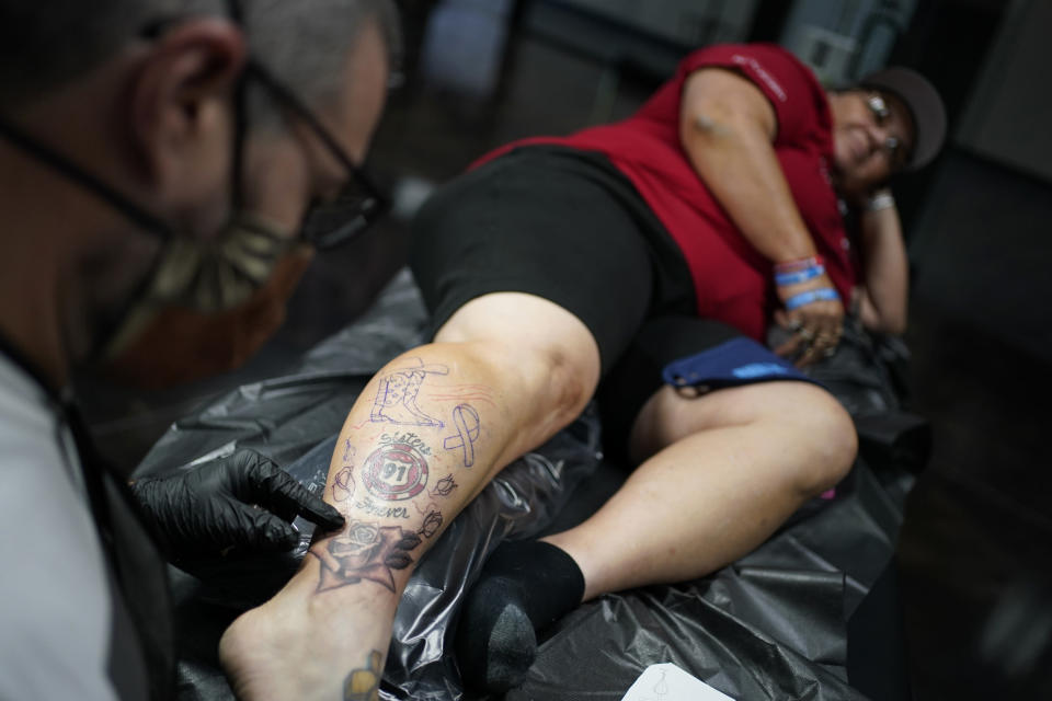 Tattoo artist Justin Warn gives a tattoo to Sue Ann Cornwell at an event put on by Healing Ink to give tattoos to survivors of the 2017 mass shooting at a country music festival in Las Vegas, Wednesday, Sept. 30, 2020, in Las Vegas. The event was held for survivors the day before the third anniversary of the deadliest shooting in recent U.S. history. (AP Photo/John Locher)