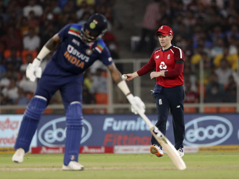 England's captain Eoin Morgan reacts after fielding a shot by India's Hardik Pandya, left during the first Twenty20 cricket match between India and England in Ahmedabad, India, Friday, March 12, 2021. (AP Photo/Aijaz Rahi)