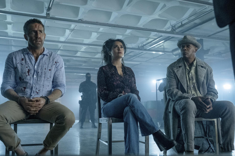 """This image released by Lionsgate shows Ryan Reynolds, from left, Salma Hayek and Samuel L. Jackson in a scene from """"The Hitman's Wife's Bodyguard."""" (David Appleby/Lionsgate via AP)"""