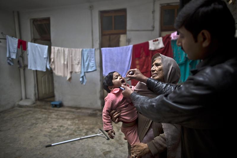 A Pakistani health worker, right, gives a polio vaccine to a child held by her grandmother at their home in Rawalpindi, Pakistan, Monday, Jan. 20, 2014. The World Health Organization said the northwestern Pakistani city of Peshawar has become the largest poliovirus reservoir in the world. (AP Photo/Muhammed Muheisen)