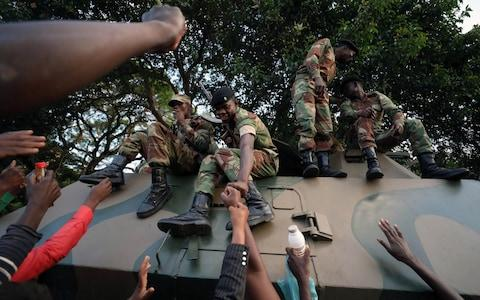 Demonstrators celebrating Mugabe's resignation reach to congratulate soldiers for their role - Credit: MIKE HUTCHINGS/REUTERS