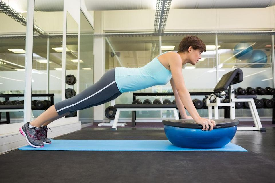 """<p>You know that your cardio sessions are crucial when it comes to burning the layer of fat sitting on top of your abdominal muscles. But it's still important to work those abs even as you're trying to shed fat, says New York City-based personal trainer Adam Sanford, founder of <a href=""""http://adamsanfordfit.com/"""" rel=""""nofollow noopener"""" target=""""_blank"""" data-ylk=""""slk:Adam Sanford Fitness"""" class=""""link rapid-noclick-resp"""">Adam Sanford Fitness</a>. His favorite move to do that? Holding plank on a <a href=""""https://www.prevention.com/fitness/workouts/g28252198/bosu-ball-exercises/"""" rel=""""nofollow noopener"""" target=""""_blank"""" data-ylk=""""slk:BOSU ball"""" class=""""link rapid-noclick-resp"""">BOSU ball</a>. </p><p>It's more challenging than a normal plank where your hands are on the floor, because the BOSU tests your balance, says Sanford. """"When your body tries to find control as your balance is challenged, your abs, obliques, and deep transverse abdominal muscles are activated,"""" he says. Strengthening these core muscles also helps increase your <a href=""""https://www.prevention.com/weight-loss/weight-loss-tips/easy-ways-boost-your-metabolism"""" rel=""""nofollow noopener"""" target=""""_blank"""" data-ylk=""""slk:metabolism"""" class=""""link rapid-noclick-resp"""">metabolism</a>, ultimately helping you to burn more calories and fat.</p><p><strong>How to do BOSU ball planks: </strong>Flip a BOSU ball on its rubber side and hold onto the edges of the flat surface with both hands, about shoulder-distance apart. Hold the plank for 30 to 45 seconds, increasing the time as you get stronger. </p>"""