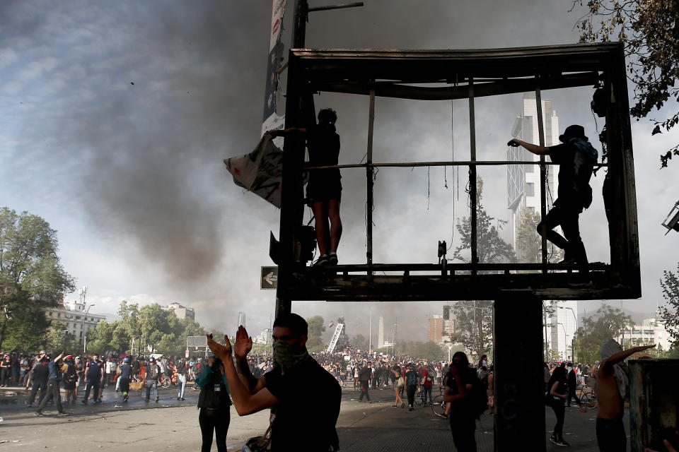 Anti-government demonstrators climb on a billboard in Santiago, Chile, Tuesday, Oct. 22, 2019. (Photo: Luis Hidalgo/AP)