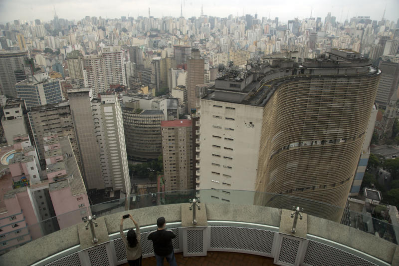 Visitors take pictures from the terrace of the Italia building in downtown Sao Paulo, Brazil, Tuesday, Nov. 26, 2013. Sao Paulo is a candidate city to host the Word Fair 2020. City boosters from Brazil, United Arab Emirates, Russia and Turkey are gathering in Paris on Wednesday to find out who will host the 2020 World Expo. At stake are billions of dollars in investment, tourism and a moment in the global spotlight. (AP Photo/Andre Penner)