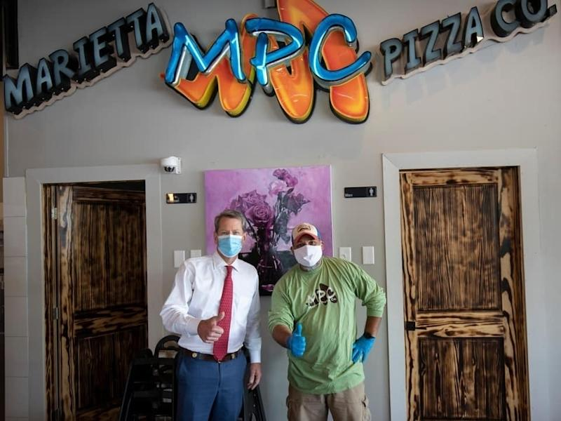 Gov. Brian Kemp is setting the example by wearing a face mask any time he's in public including during a visit Friday to the Marietta Pizza Co. with owner David Contreras.