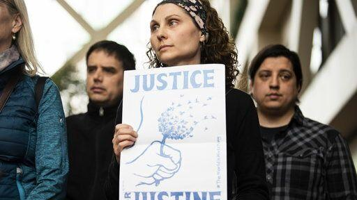 """A woman holds a sign that reads """"Justice for Justine."""" (Photo: Yahoo View)"""