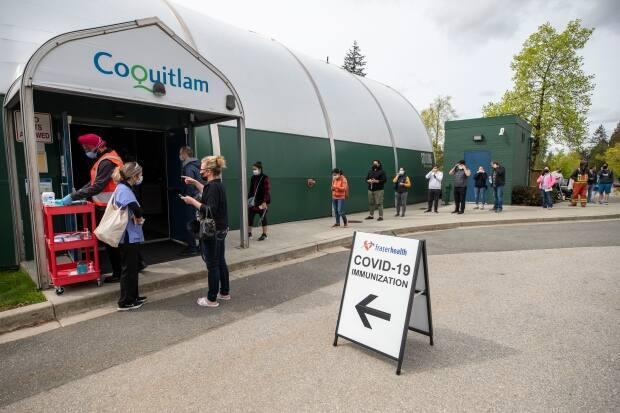 Hundreds of people lined up outside the Poirier Forum in Coquitlam, B.C., on Tuesday after Fraser Health announced a pop-up vaccine clinic.  (Ben Nelms/CBC - image credit)