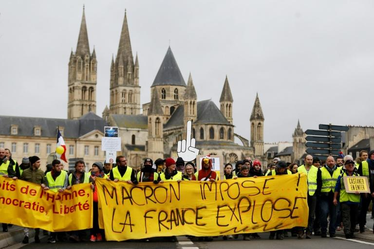 "Yellow Vest protesters with a banner reading ""Macron raises taxes, France explodes,"" in Caen, northwestern France"