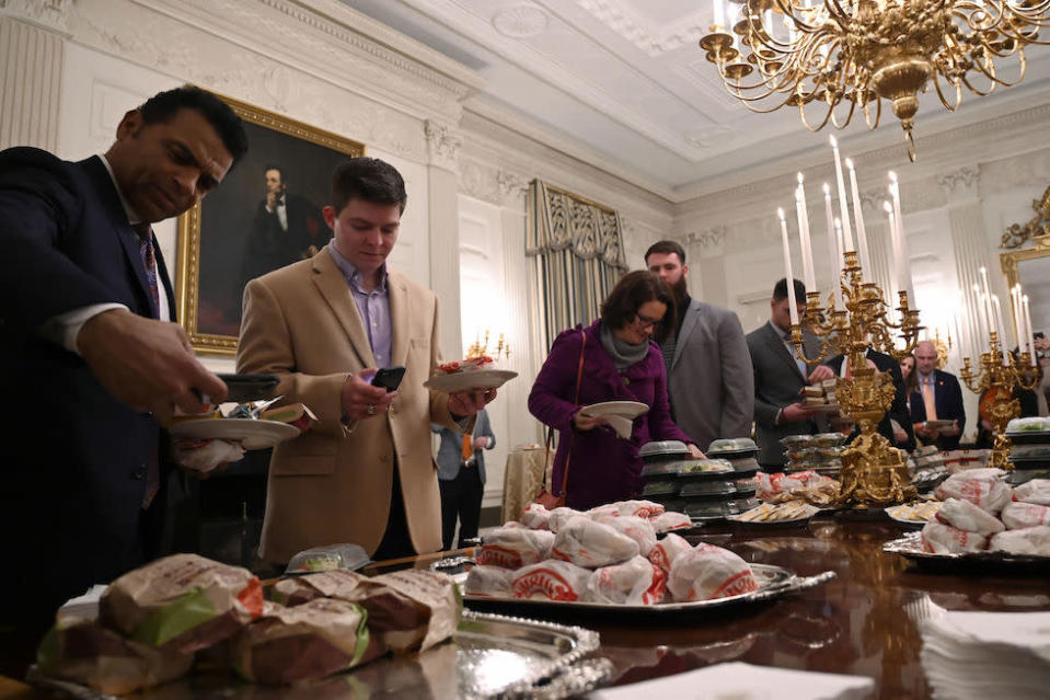 Guests attending a reception for the Clemson Tigers grab fast food sandwiches in the State Dining Room of the White House (Picture: AP)