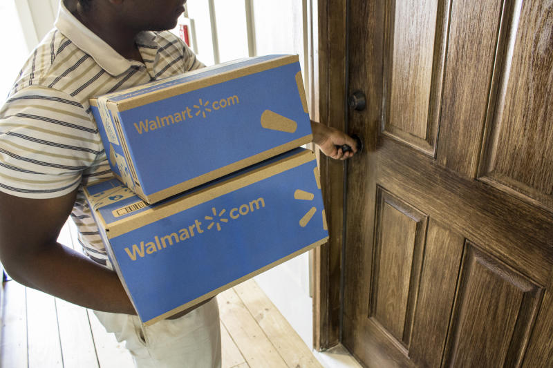 A man holding Walmart.com boxes and about to turn a doorknob.
