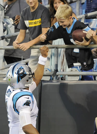 Carolina Panthers' Cam Newton, left, gives a fist-bump to a fan after giving him a football after a touchdown pass against the Chicago Bears during the first half of a preseason NFL football game in Charlotte, N.C., Friday, Aug. 9, 2013. (AP Photo/Mike McCarn)