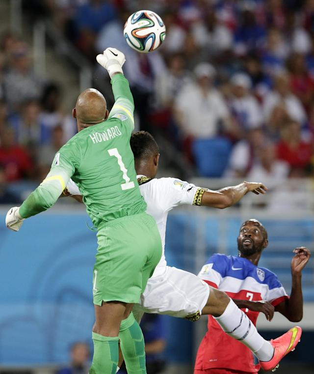 United States' goalkeeper Tim Howard, left, punches the ball away from Ghana's Andre Ayew, center, during the group G World Cup soccer match between Ghana and the United States at the Arena das Dunas in Natal, Brazil, Monday, June 16, 2014. (AP Photo/Petr David Josek)