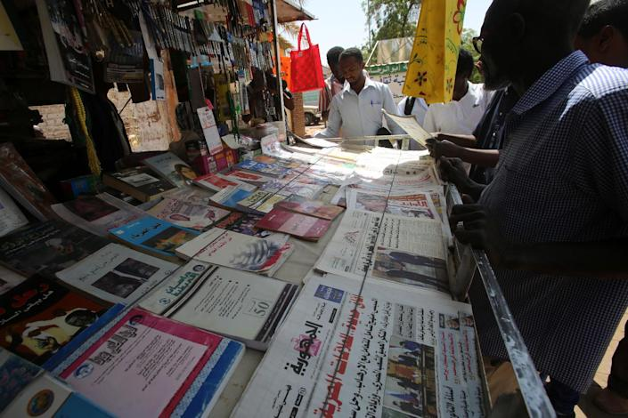 Sudanese men look at newspapers displayed at a kiosk in the capital Khartoum on February 16, 2015 (AFP Photo/Ashraf Shazly)