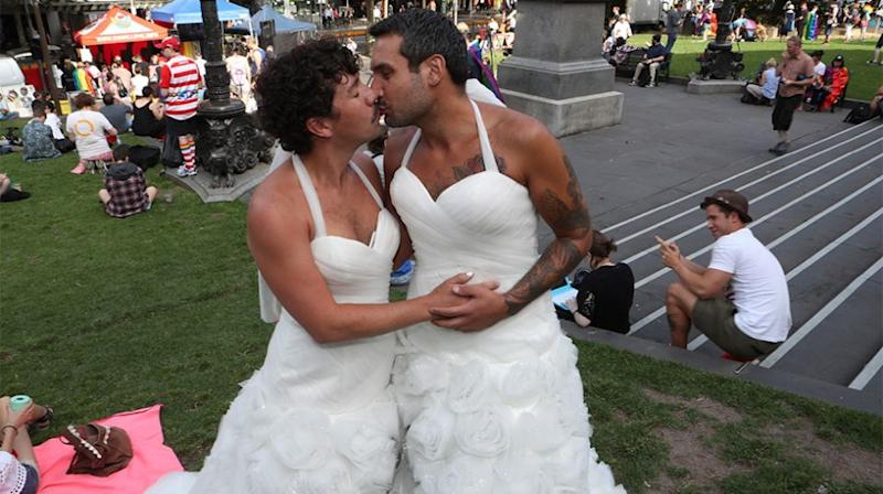 Two men dresses as brides are seen as people begin to gather in front of the State library of Victoria for the outcome of the Same Sex Marriage postal survey. Source: AAP