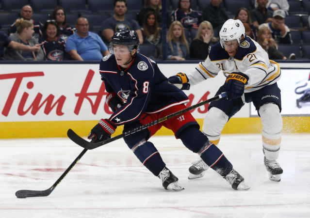 Columbus Blue Jackets defenseman Zach Werenski, left, controls the puck against Buffalo Sabres forward Kyle Okposo during the third period of an NHL preseason hockey game in Columbus, Ohio, Tuesday, Sept. 17, 2019. The Blue Jackets won 4-1. (AP Photo/Paul Vernon)