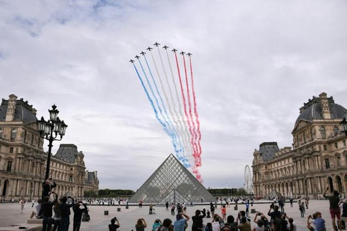 The Patrouille de France, the air force's elite acrobatic flying team, performed a display of the national flag (AFP Photo/Anne-Christine POUJOULAT)