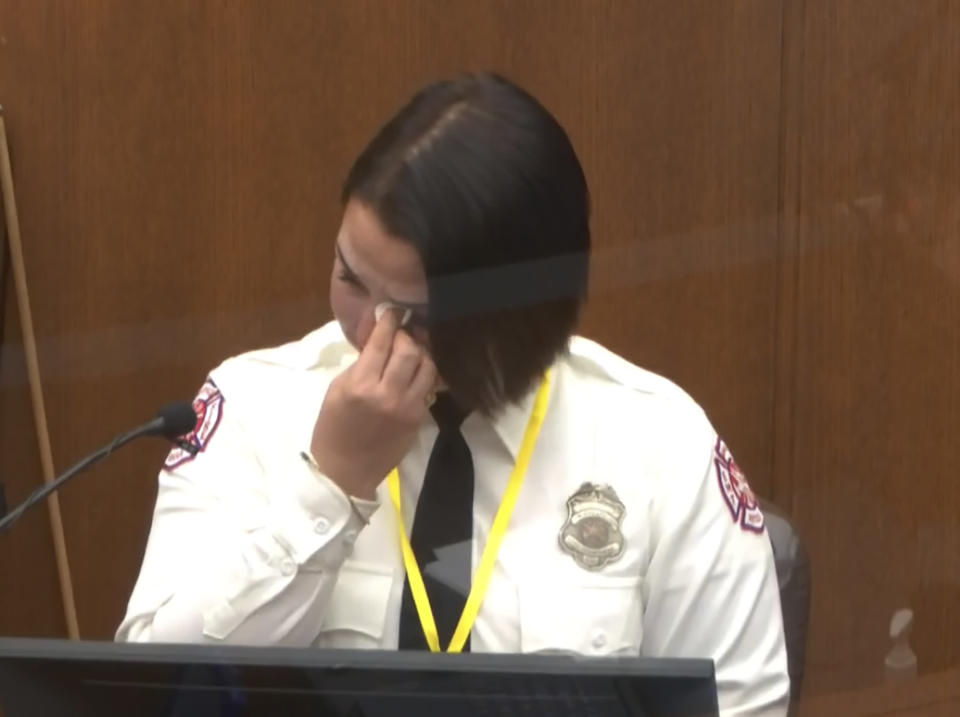 In this image from video, Minneapolis Firrefighter Genevieve Hansen, wipes her eyes as she testifies as Hennepin County Judge Peter Cahill presides Tuesday, March 30, 2021, in the trial of former Minneapolis police Officer Derek Chauvin, in the May 25, 2020, death of George Floyd at the Hennepin County Courthouse in Minneapolis, Minn. (Court TV via AP, Pool)