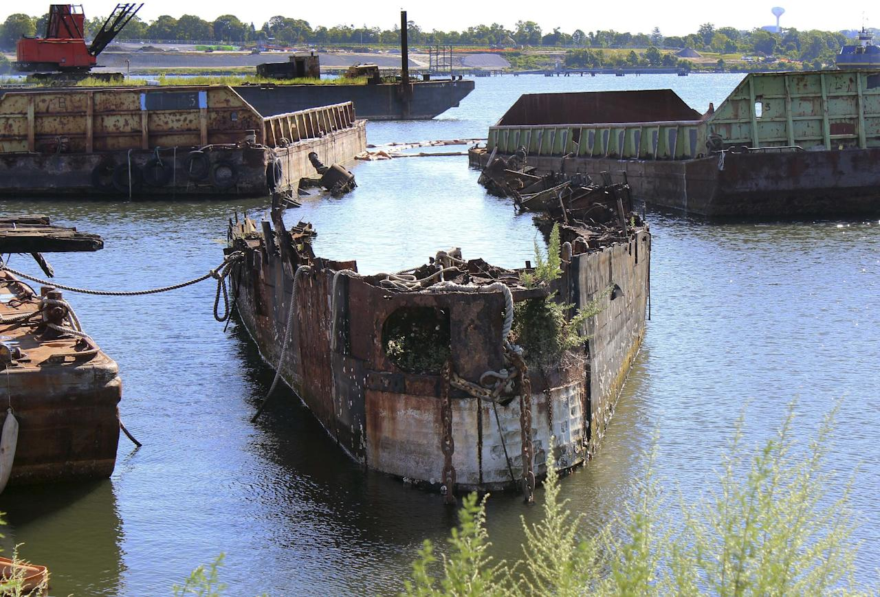 "In this Monday, Aug. 22, 2016 photo, rusting remnants of an old Russian submarine that once was used as a floating museum until it sank in 2007 remains in the Providence river in Providence, R.I. The state wants it gone. Known as Juliett 484, the sub served as a set for the 2002 Harrison Ford movie ""K-19: The Widowmaker."" It was moved in 2009 to a scrap metal facility, but the company stopped working on it in 2014. (AP Photo/Jennifer McDermott)"