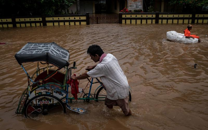 A man pushes a rickshaw through the flooded area effected by the tsunami on December 26, 2018  - Getty Images AsiaPac