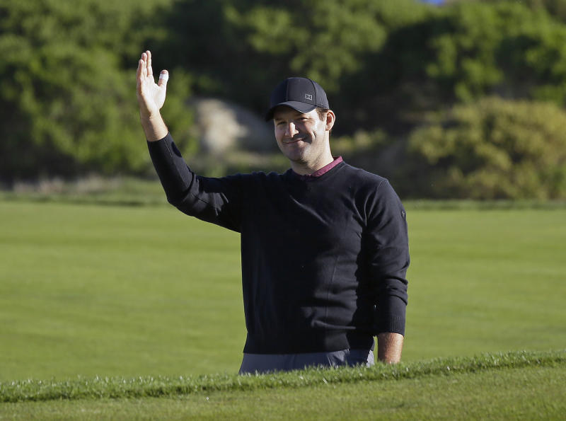 FILE - In this Feb. 9, 2018, file photo, Tony Romo waves after hitting the ball out of a bunker and close to the pin on the 11th green of the Monterey Peninsula Country Club Shore Course during the second round of the AT&T Pebble Beach National Pro-Am golf tournament, in Pebble Beach, Calif. Romo is finally in the Super Bowl. After being unable to lead Dallas to the big game, Romo will call the game for CBS in his second season in the booth. But just like Jared Goff and Tom Brady, Romo is coming in with plenty of momentum after his call of the AFC Championship game _ where he predicted many of New England's plays and tendencies _ drew universal accolades. (AP Photo/Eric Risberg, File)