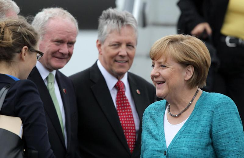 German Chancellor Angela Merkel, right, is greeted by officials as she arrives at Belfast International Airport, in Northern Ireland, on Monday, June 17, 2013. President Hollande is in Northern Ireland to attend the G-8 Summit in Enniskillen. (AP Photo/ Peter Muhly, Pool)