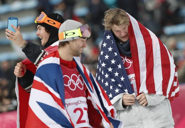 Snowboarding - Pyeongchang 2018 Winter Olympics - Men's Big Air Finals - Alpensia Ski Jumping Centre - Pyeongchang, South Korea - February 24, 2018 - Sebastien Toutant of Canada, Kyle Mack of the U.S., and Billy Morgan of Britain celebrate with their national flags. REUTERS/Murad Sezer