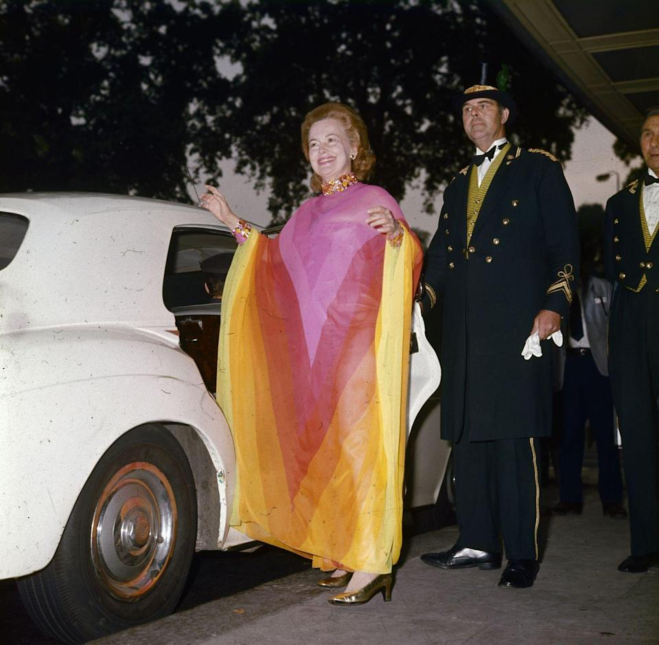 """<p>Leaving London's famed Dorchester Hotel, Olivia wore a bold gown to meet <a href=""""https://www.townandcountrymag.com/society/tradition/a29894927/prime-minister-edward-heath-the-crown-facts/"""" rel=""""nofollow noopener"""" target=""""_blank"""" data-ylk=""""slk:British prime minister Edward Heath"""" class=""""link rapid-noclick-resp"""">British prime minister Edward Heath</a> in 1971. </p>"""
