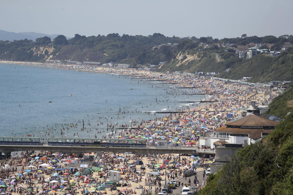 Crowds gather as hot weather draws crowds to the beach in Bournemouth, England, Thursday June 25, 2020. Coronavirus lockdown restrictions are being relaxed but people should still respect the distancing requirements between family groups. According to weather forecasters this could be the UK's hottest day of the year, so far, with scorching temperatures forecast to rise even further. (Andrew Matthews/PA via AP)