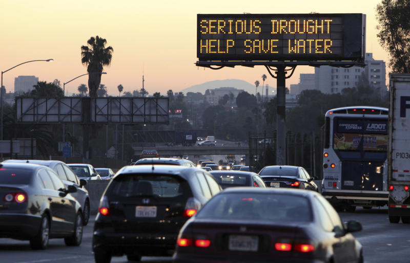 FILE - In this Feb. 14, 2014, file photo, morning traffic makes its way toward downtown Los Angeles along the Hollywood Freeway past an electronic sign warning of severe drought. California water managers will vote on Feb. 20, 2018, whether to reinstate some water restrictions and conservation campaigns and make them permanent, as a year with no almost no rain plunges Southern California back into drought and sends water use there climbing to levels above those of the state's historic 2013-2017 drought. (AP Photo/Richard Vogel, File)
