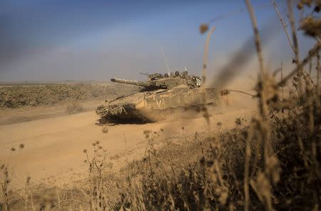 Israeli soldiers ride atop a tank near the border with Gaza July 27, 2014. REUTERS/Siegfried Modola