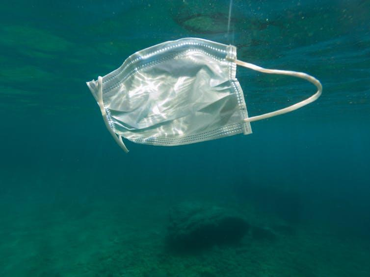 A face mask floating underwater at sea.