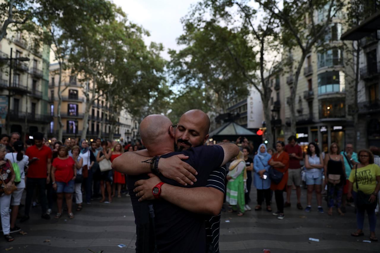 "A Muslim man gives hugs next to a sign reading ""I am Muslim, I am not a terrorist. I share hugs of love and peace"" (not pictured), at where a van crashed into pedestrians at Las Ramblas in Barcelona, Spain, August 20, 2017. REUTERS/Susana Vera"