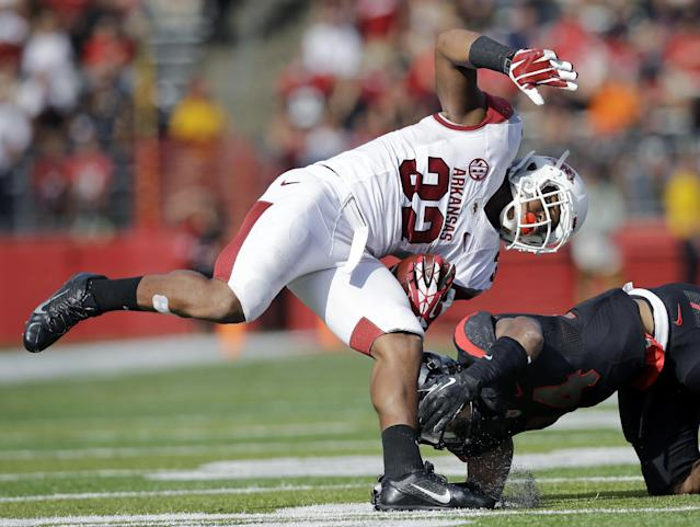 Arkansas running back Jonathan Williams (32) is upended by Rutgers defensive back Lew Toler during the first half of an NCAA college football game in Piscataway, N.J., Saturday, Sept. 21, 2013. (AP Photo/Mel Evans)