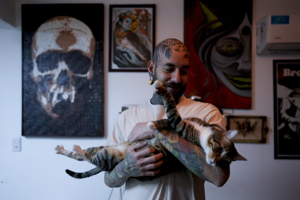 Tulio holds his cat at home in Buenos Aires, Argentina, Wednesday, Sept. 8, 2021. Tulio adopted two cats during the COVID-19 lockdown for their companionship during months at home. (AP Photo/Natacha Pisarenko)