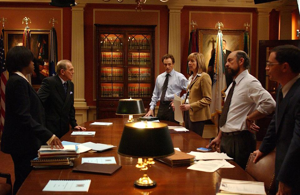 Michael Hyatt as Angela Blake, John Spencer as Leo, Bradley Whitford as Josh, Allison Janney as C.J., Richard Schiff as Toby and Joshua Malina as Will standing at conference table in S5 E8 of 'The West Wing' (Warner Bros.)