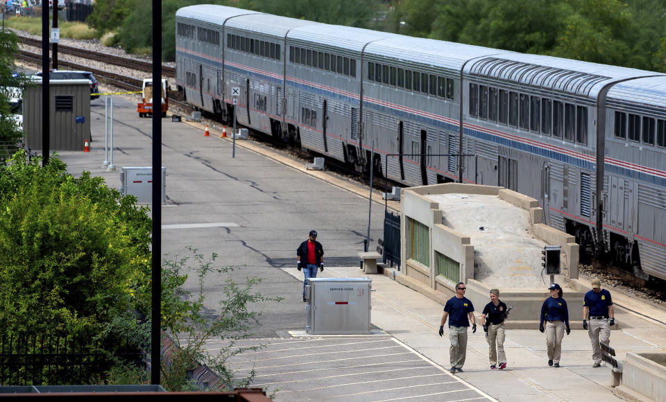 Federal Bureau of Investigation agents work at the crime scene after a shooting aboard an Amtrak train in downtown Tucson, Ariz., on Monday, Oct. 4, 2021. (Rebecca Sasnett/Arizona Daily Star via AP)