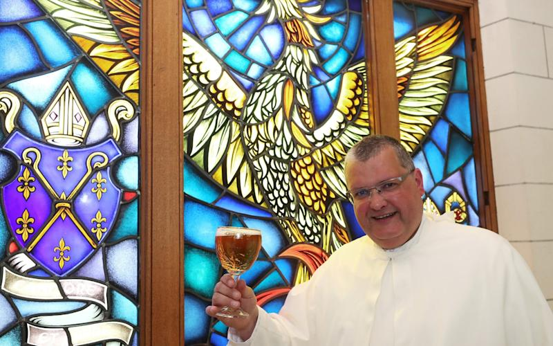 Norbertine Father Karel poses with a Grimbergen beer, symbolised by a phoenix, in the courtyard of the Belgian Abbey of Grimbergen - REUTERS