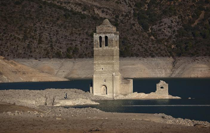 . A church and remains of an ancient village which are usually covered by water are seen inside the reservoir of Mediano, in Huesca, Spain, Tuesday March 13, 2012. The reservoir built in the 1950s, submerging a village called Mediano and its 16th century church, is so low on water that the ruins of buildings which are usually under water are now uncovered. Spain is suffering the driest winter in more than 70 years, adding yet another woe for an economically distressed country that can scarcely afford it. Thousands of jobs and many millions of euros could be in jeopardy. (AP Photo/Emilio Morenatti)
