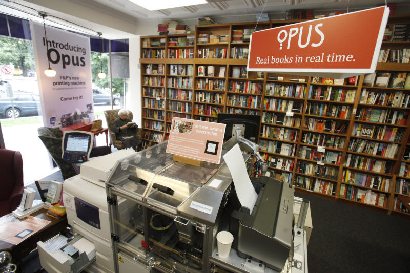 In this June 5, 2012, photo, a customer reads a book by the Espresso Book Machine, known as Opus, at Politics and Prose bookstore in Washington. Self-publishing has been made easier since the machine by On Demand Books debuted in 2006. The machine also can makes copies of out-of-print editions. The first machine was installed briefly at the World Bank's bookstore. Through a partnership with Xerox, the company now has machines in about 70 bookstores and libraries across the world including London; Tokyo; Amsterdam; Abu Dhabi, United Arab Emirates; Melbourne, Australia; and Alexandria, Egypt. (AP Photo/Jacquelyn Martin)